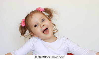 Funny child girl child shows tongue, smiles and laughs. Baby...