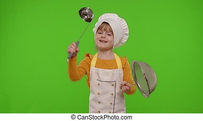 Funny Caucasian preschooler child girl kid dressed as cook chef baker in apron dancing with sieve and ladle, fooling around isolated on chroma key background. Cooking school, children education. 4k