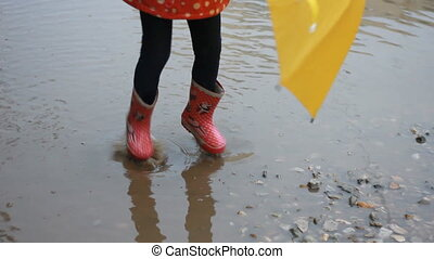 Funny child girl jumping and playing in puddles in rainy...
