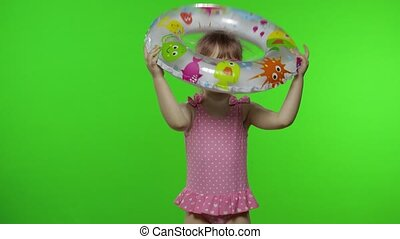 Portrait of funny child girl with inflatable circle. Pink hair kid with in swimwear, sunglasses holds swimming ring. Isolated on chroma key green screen background. Copy space. Vacation on sea concept