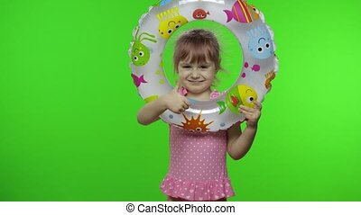 Portrait of funny child girl with inflatable circle. Pink hair kid with in swimwear holds swimming ring. Isolated on chroma key green screen background. Copy space. Vacation on sea concept