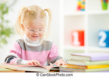 Funny child in eyeglases reading book at home