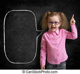 Funny child in eyeglasses standing near school chalkboard as a teacher with blank speech bubble scetch.