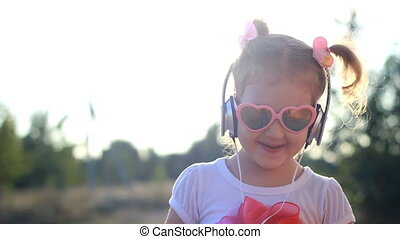 Funny child in headphones listens to music, sings and dances. Lovely girl in sunglasses at sunset on a summer day. Lifestyle
