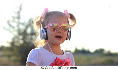 Funny child in headphones listens to music, sings and dances. Lovely girl in sunglasses at sunset on a summer day.