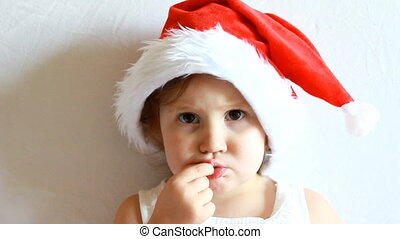 Funny child in Santa Claus hat close-up. The concept of Christmas