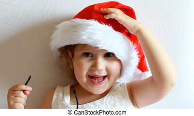 Funny child in Santa Claus hat. The concept of Christmas and New Year. Magic