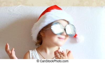 Funny child in Santa Claus hat. The concept of Christmas. Magic