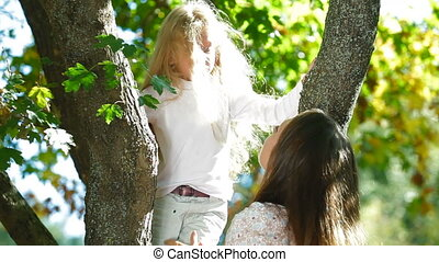 Young mother and little daughter having fun in the park, child kissing his mom
