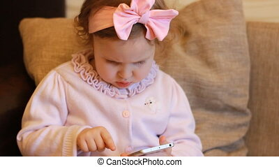 Funny child looks on the mobile phone screen and plays...