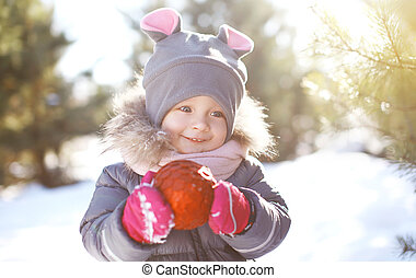 Funny child outdoors in sunny winter day