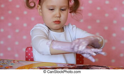Funny child paints his hands with paint. Baby artist. Little girl draw body art.