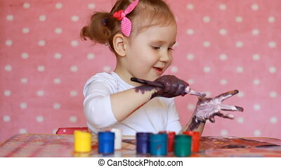 Funny child paints his hands with paint. Baby artist. Little girl draws art