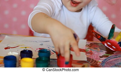 Funny child paints his hands with paint. Baby artist. Little girl draws art.