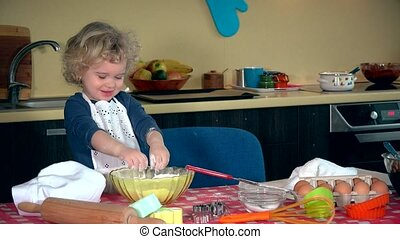 Funny child plays with flour. Girl knead dough. Girl funny...