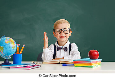 funny child   schoolboy    student  raises his hand up near school blackboard