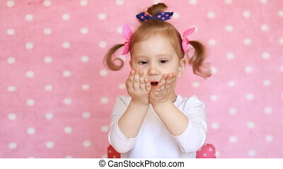 Funny child send kiss. Sweet little girl child sends air kisses. Pink background