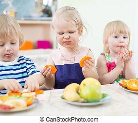 Funny children eating fruits in kindergarten