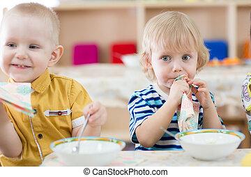 Funny children eating in kindergarten