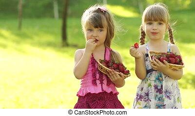 Funny children girl eating strawber