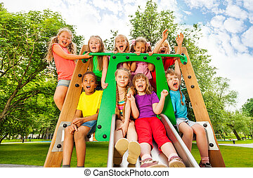 Many happy funny, diverse looking children on playground chute with arms up and laughing, screaming in happiness