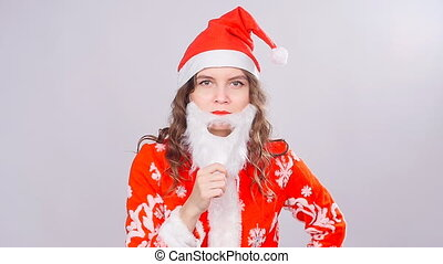 Funny Christmas girl with red fluffy Santa Hat and beard -...