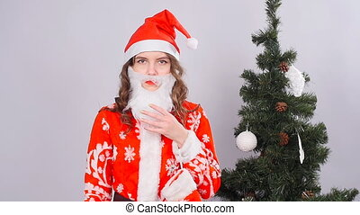 Funny Christmas girl with red fluffy Santa Hat and beard