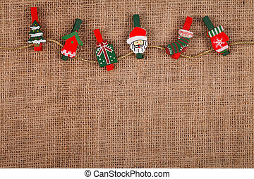 Little funny Christmas ornaments on golden thread, burlap background