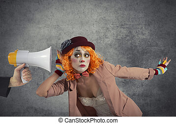 Funny clown hears a megaphone with a message