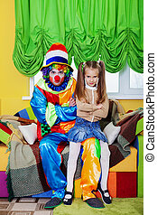 Funny clown with the little girl sit on a sofa.