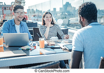 Funny college mates laughing while studying together