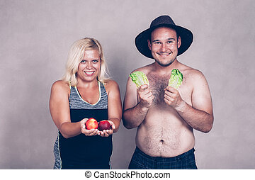 Funny corpulent couple with fruit and vegetable
