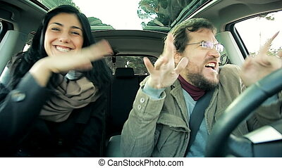 Funny man and woman dancing like crazy driving car
