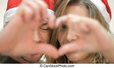 Funny couple in Santa hat peeking through the heart of the fingers