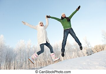 Funny couple jumping on a snowy background