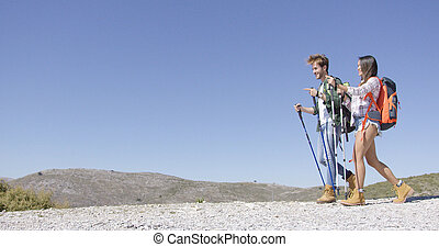 Funny couple walking with trekking poles