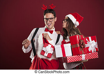 Funny couple with stack of christmas gifts