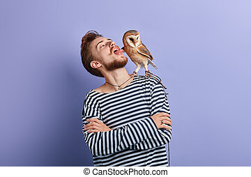 funny crazy man putting tongue out, looking at the owl