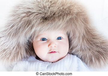 Funny curious baby girl in a huge winter hat
