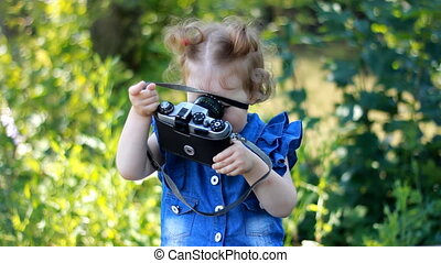 Funny curious baby girl is holding in hands retro  and photographing in the park. Happy child. Photographer, photosession, photography.
