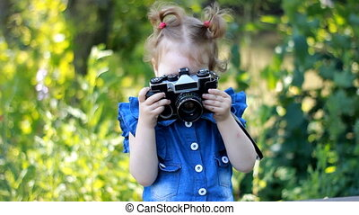 Funny curious baby girl is holding in hands retro ?????? and photographing in the park. Happy child. Photographer, photosession, photography.