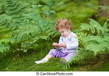 Funny curly baby girl eating wild raspberries in a beautiful aut
