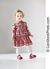 Funny curly baby girl in a red dress walking with a cookie in he