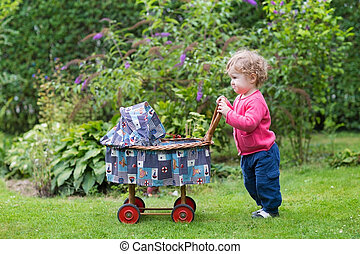 Funny curly baby girl playing with a vintage doll stroller in th