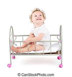 Funny curly baby paying in a doll bed, on white background