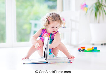 Funny curly toddler girl in a pink dress reading a book