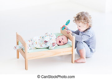 Funny curly toddler girl playing with hew newborn baby...