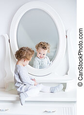 Funny cute baby girl watching her reflection in a white bedroom