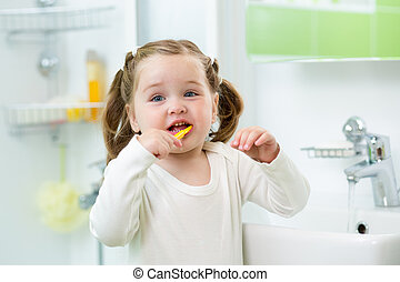 funny cute child girl brushing teeth in bathroom