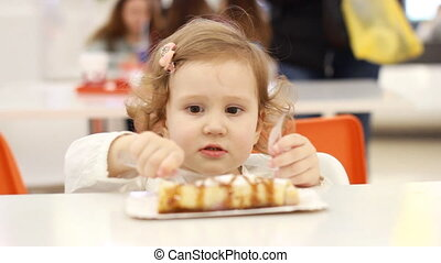 Funny cute child in a cafe eating food - dessert pancakes...